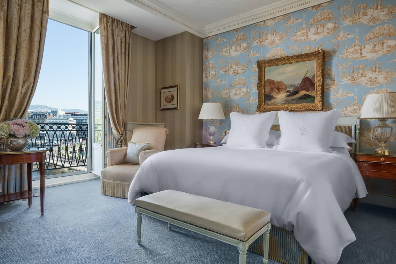 Suite Léman with antique-style blue wallpaper, painting with gold frame above bed next to open French doors with lake view