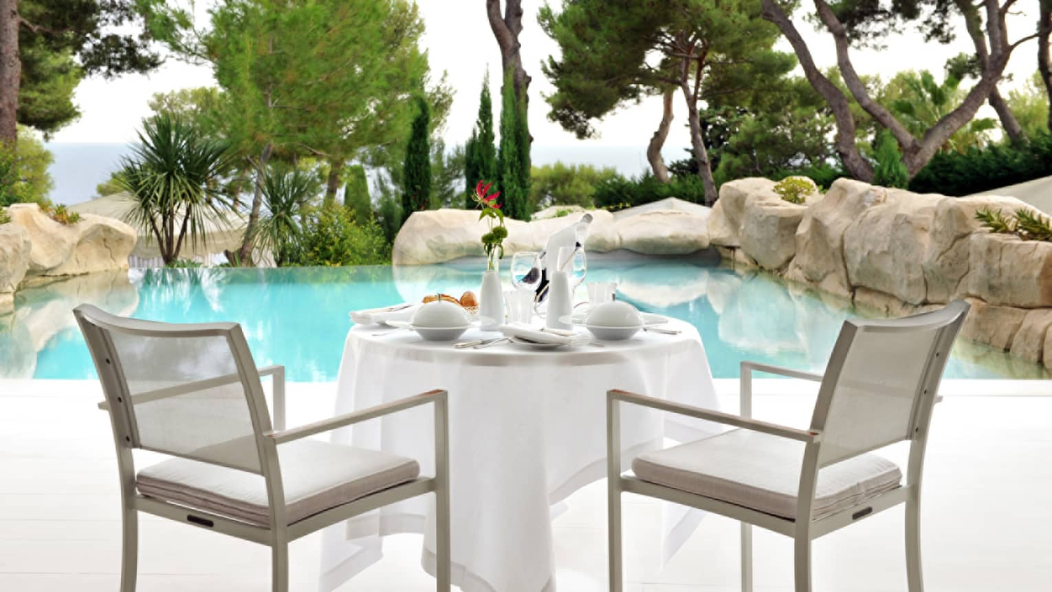 Private dining table room service on hotel suite patio by swimming pool