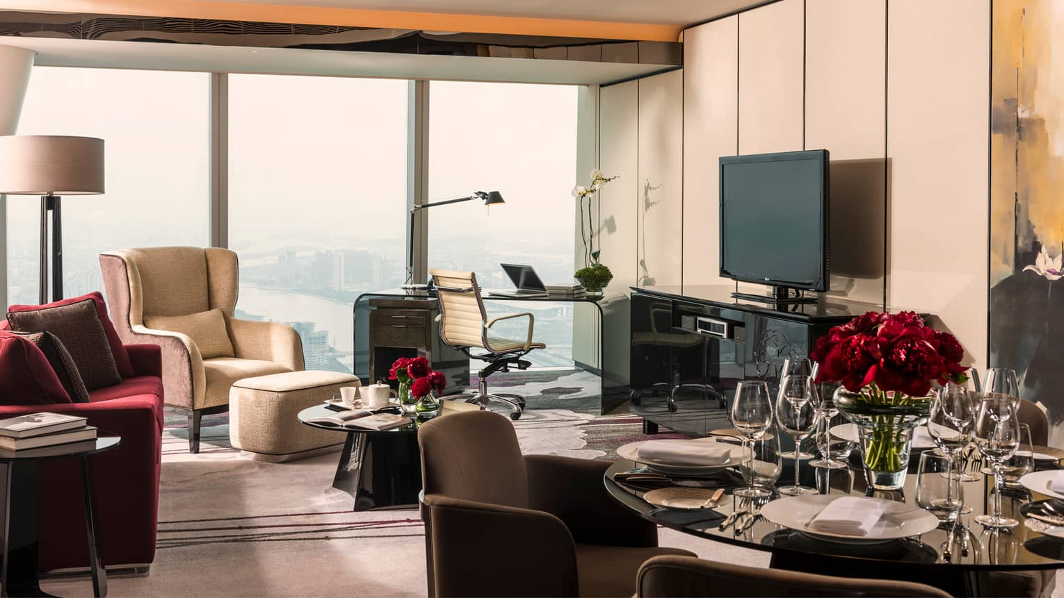 Deluxe Suite living area with round glass dining table, red sofa and desk by window with unobstructed city views