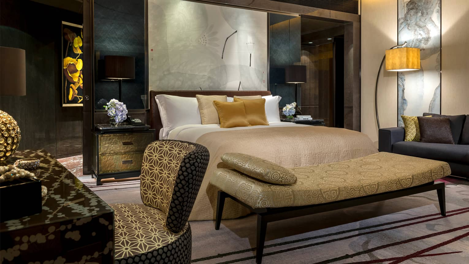 Hotel room at night with dark brown and cream decor, gold accent pillows and bench, modern art