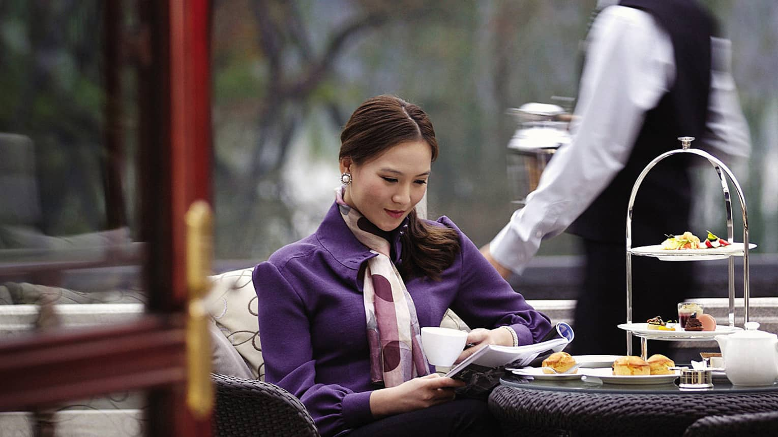 Woman wearing purple coat, seated at afternoon tea in Lobby Lounge, staff member behind