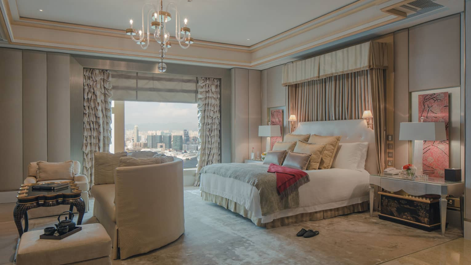 Spacious Hong Kong hotel room bed with curtains above headboard, crystal chandelier, curved loveseat