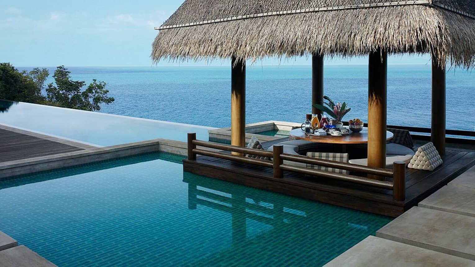 Patio cabana with thatched-roof by small plunge swimming pool overlooking ocean