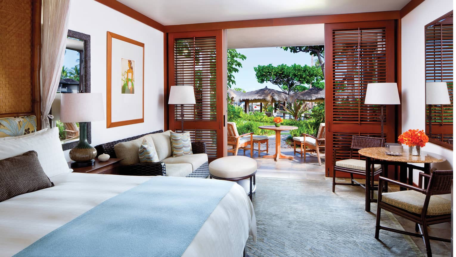 Poolside Room bed with blue blanket, wicker loveseat and ottoman, table, open wood patio shutters
