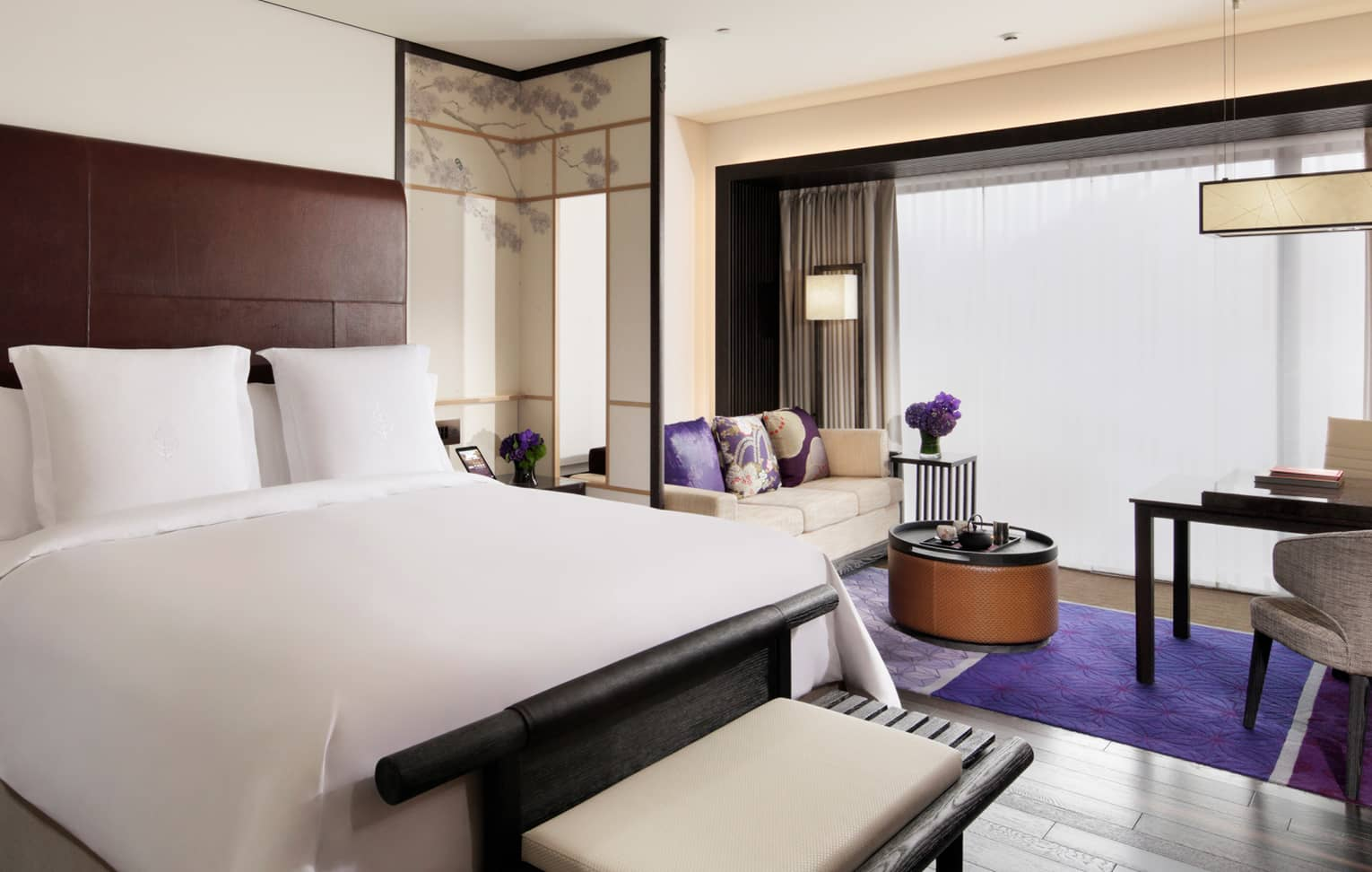 Premier Room with white bed, bench and loveseat, bright purple pillows and rug