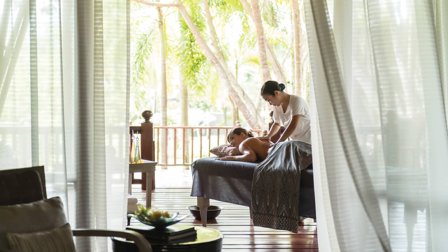 Spa staff massages woman's back, shoulders on table by sheer white curtains