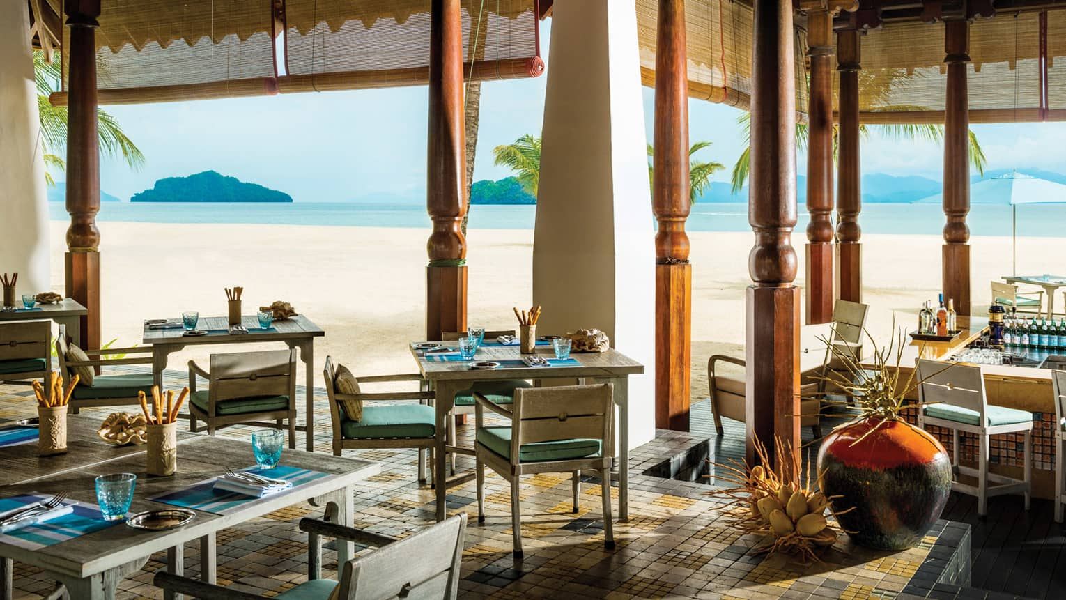 Dining tables, chairs under tall carved wood pillars with open-air walls to beach