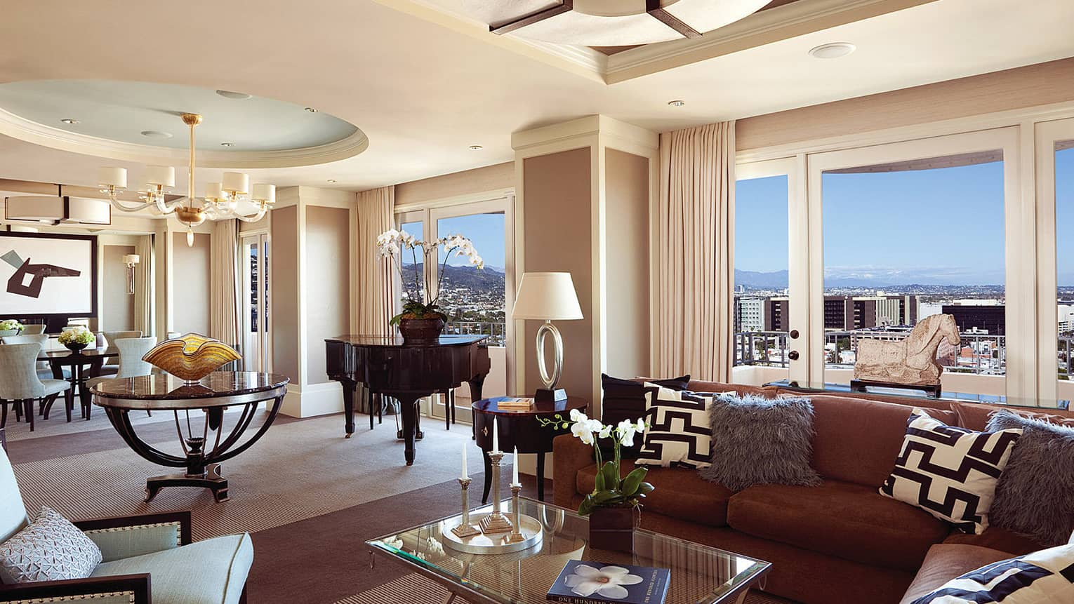 Presidential Suite East large living, dining room under soaring ceiling, picture windows with views of city, hills