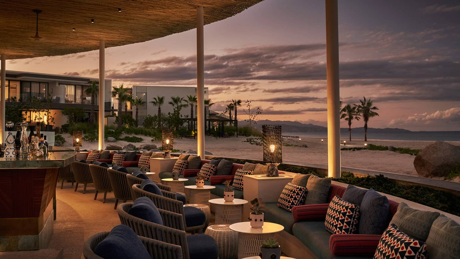 Dimly lit Casa de Brasa lounge area overlooking beach with palm trees at dusk