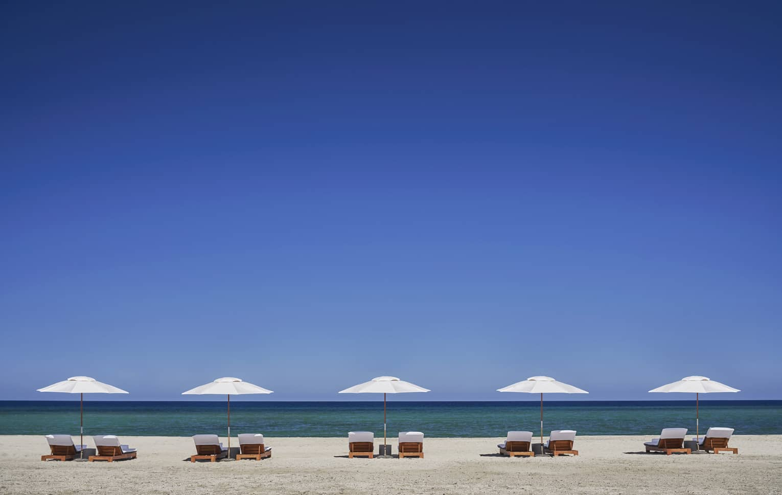 Row of white patio umbrellas, chairs on beach against striking blue sky
