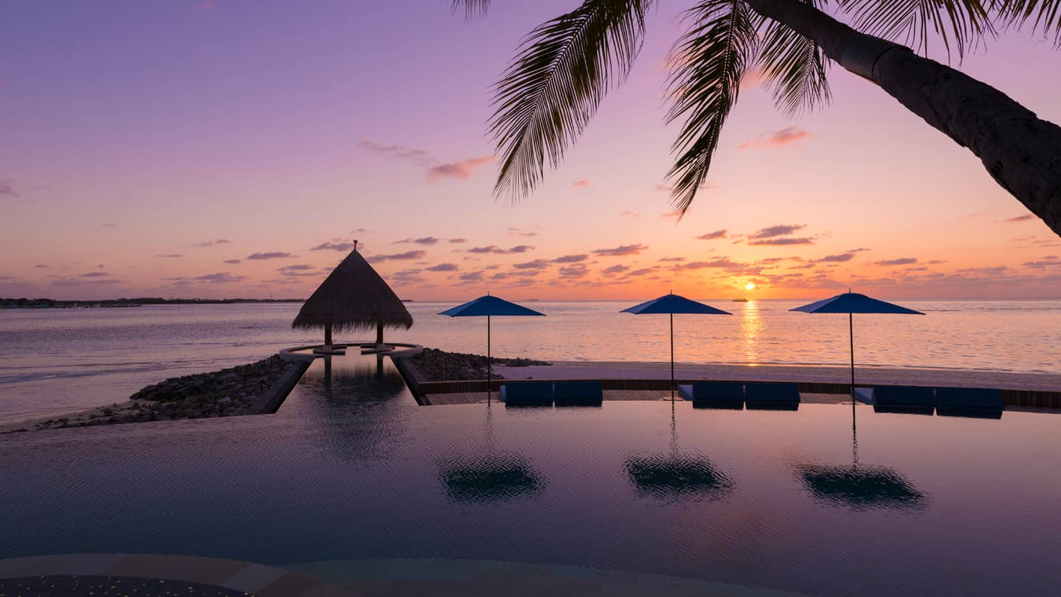 Sunset view of outdoor infinity pool near the beach