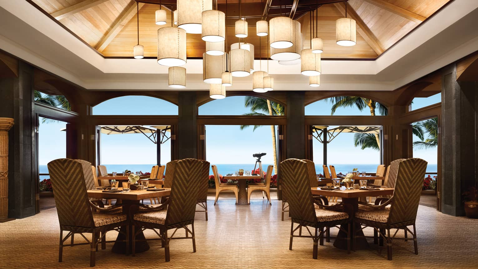 Views Restaurant dining room, tables and chairs under vaulted ceilings with modern lanterns