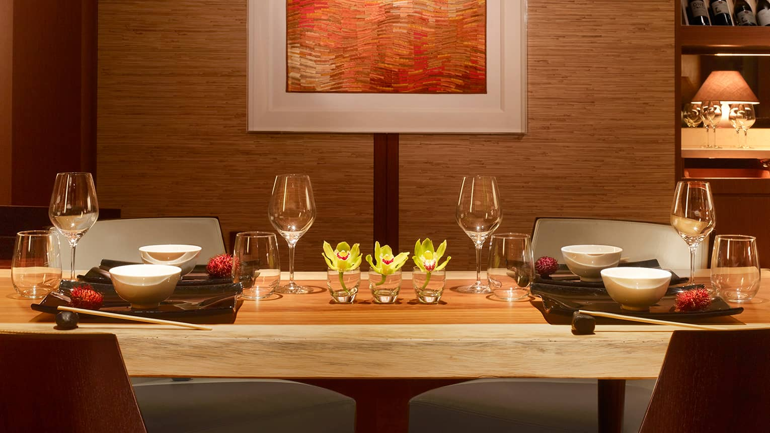 Long rustic wood private dining table with wine glasses, yellow flowers under wall with orange art