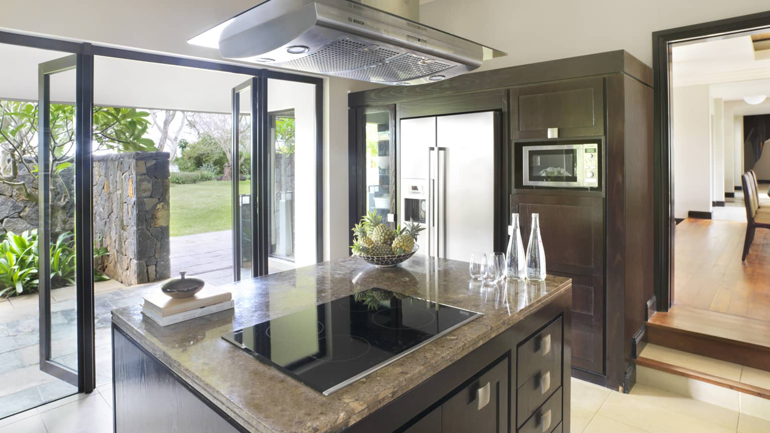 Stove range on marble island in modern kitchen, open glass walls to patio