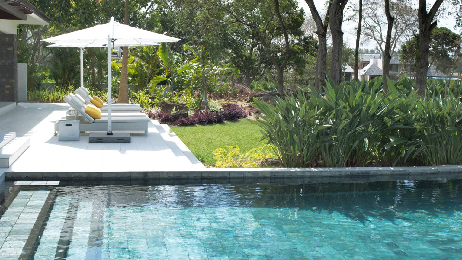 Stone steps leading into villa plunge pool, two white lounge chairs, umbrella on deck
