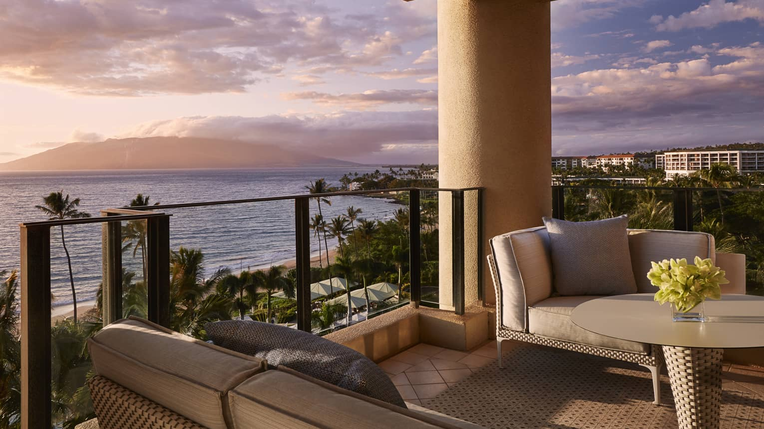 Outdoor terrace with sofa, arm chair, glass railing, looking out to sunset over ocean