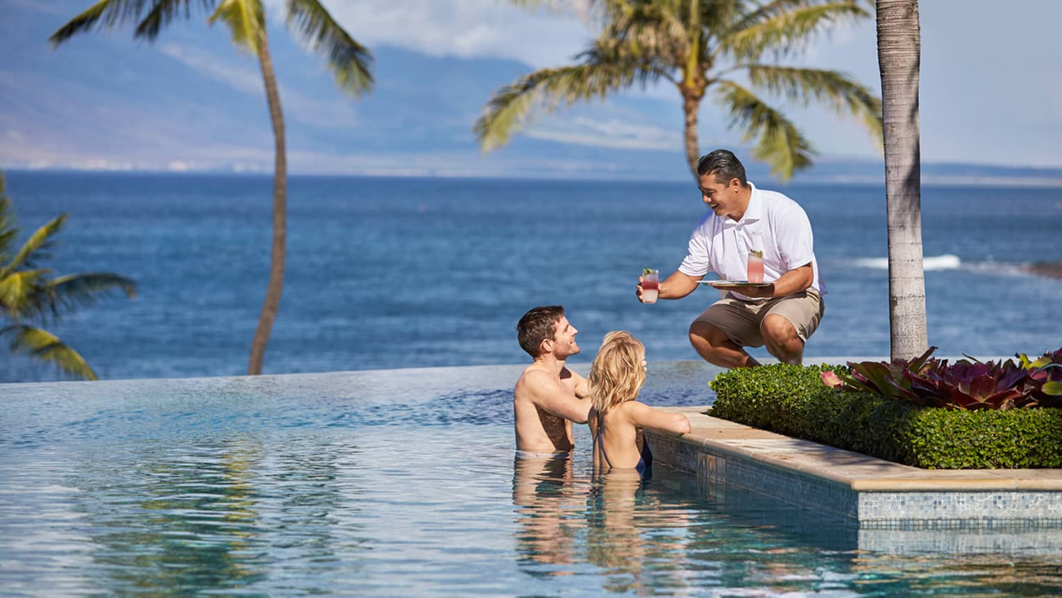 Server in white uniform with tray passes a cocktail to man and woman at edge of infinity swimming pool