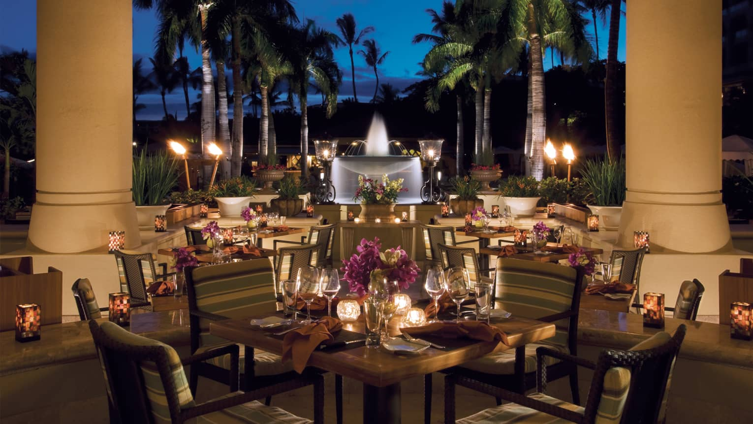 DUO Steak and Seafood outdoor dining tables at night with glowing candles by white pillars, white fountain