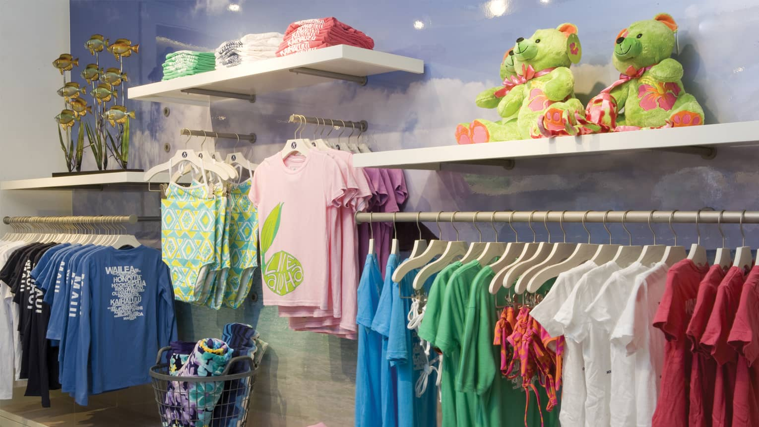 Wall of clothing boutique with racks of children's clothes on hangers, toys and towels
