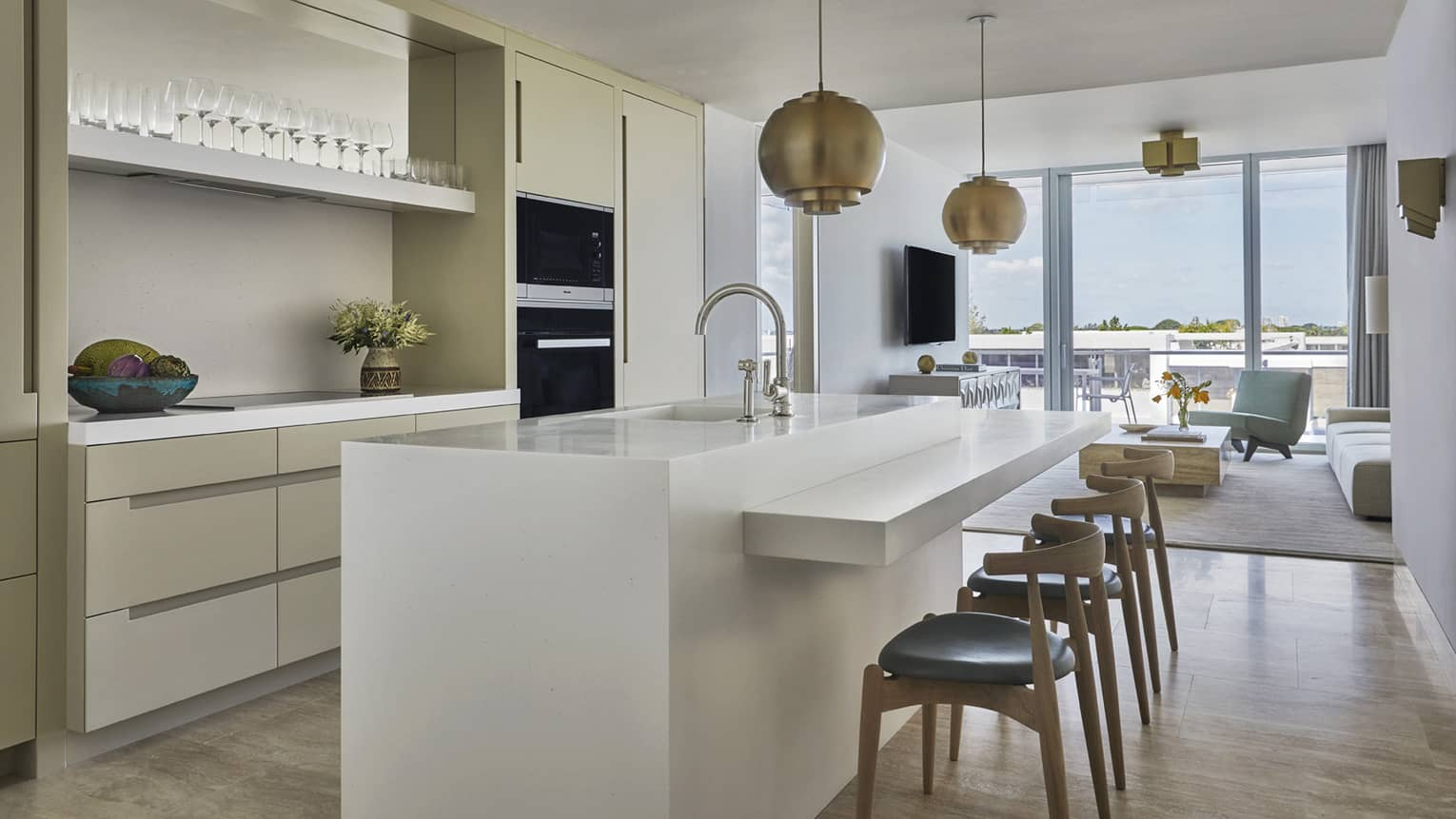 Long white island counter with stools in bright, modern kitchen