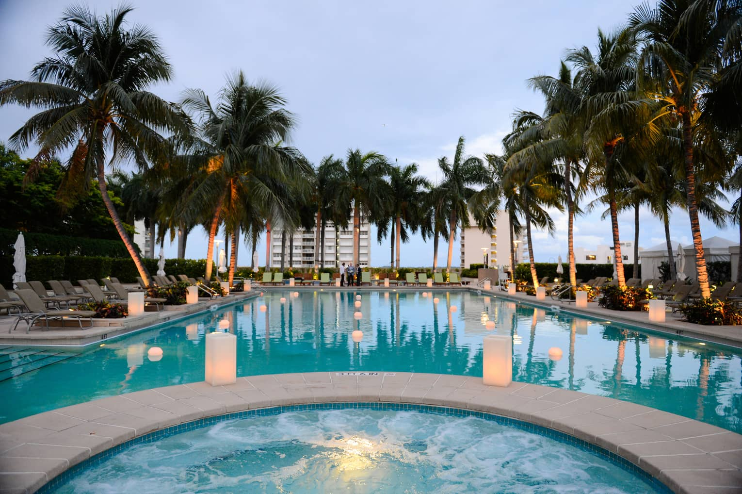 White lanterns glow along outdoor pool lined with palm trees