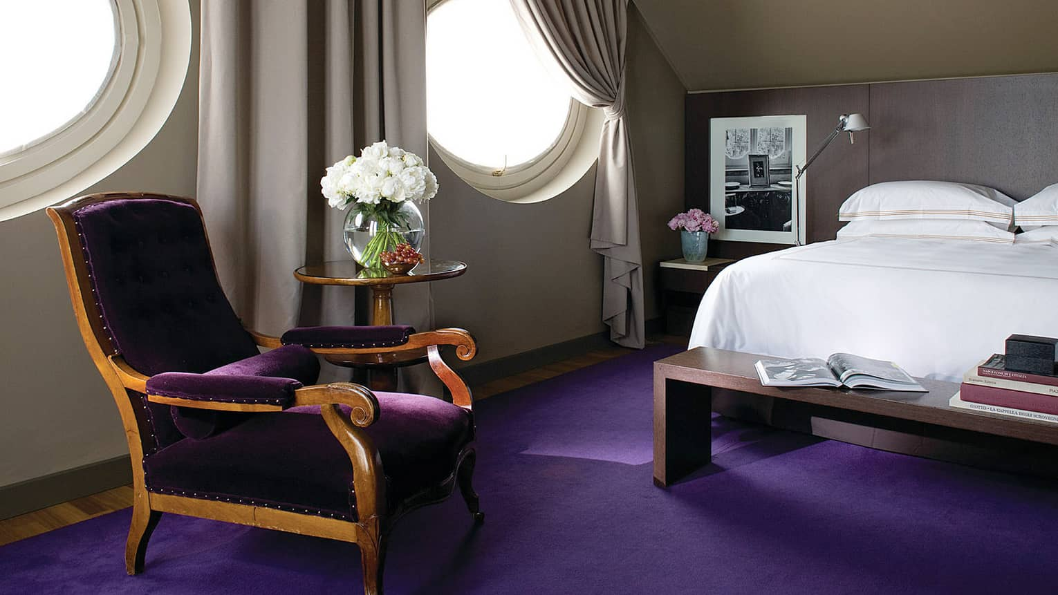 Designer Suite circular windows over purple velvet chair, carpet, bed with wood bench, books
