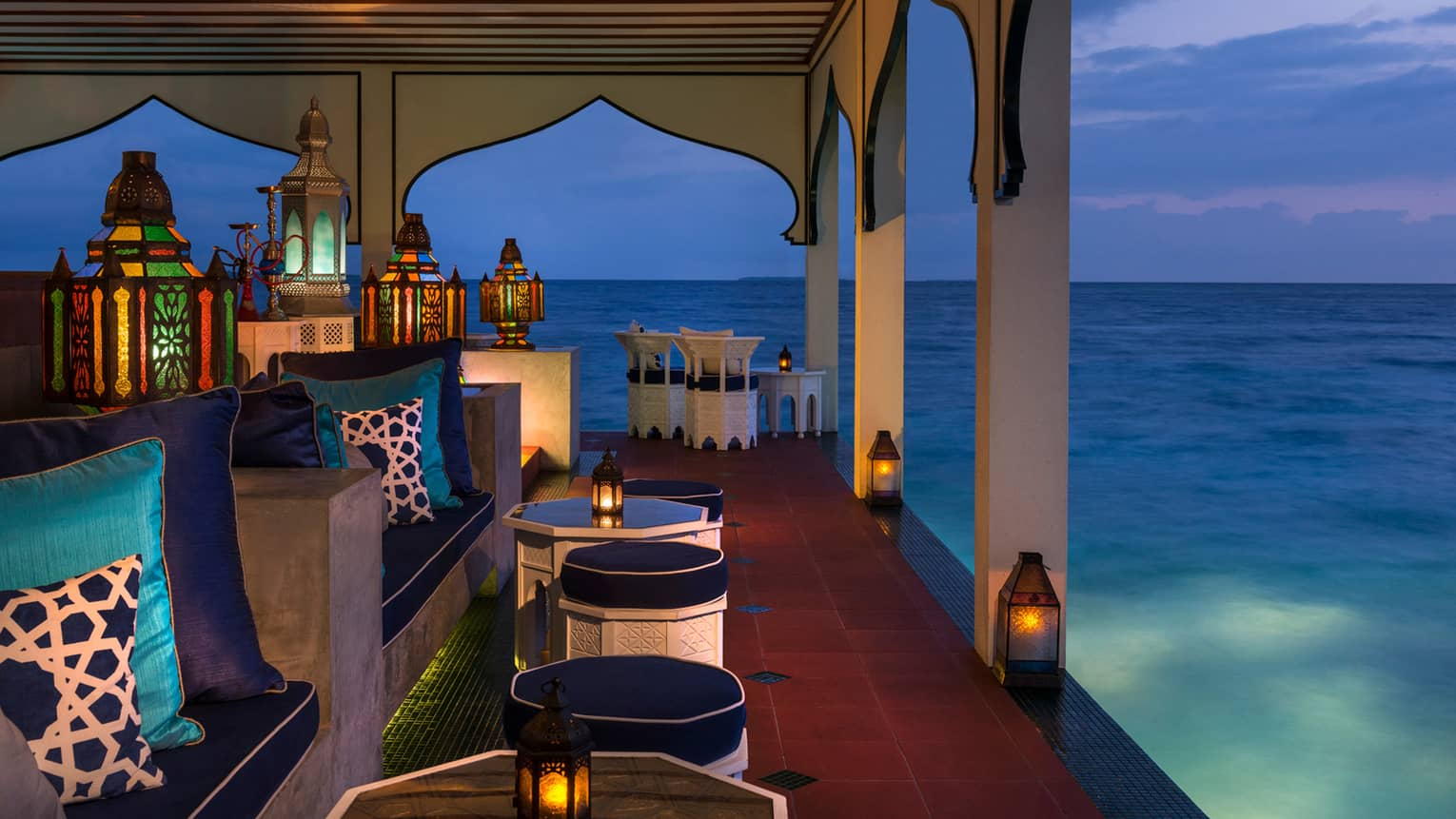 Shisha Bar patio with glowing Moroccan lanterns over plush blue benches, silk pillows, over lagoon