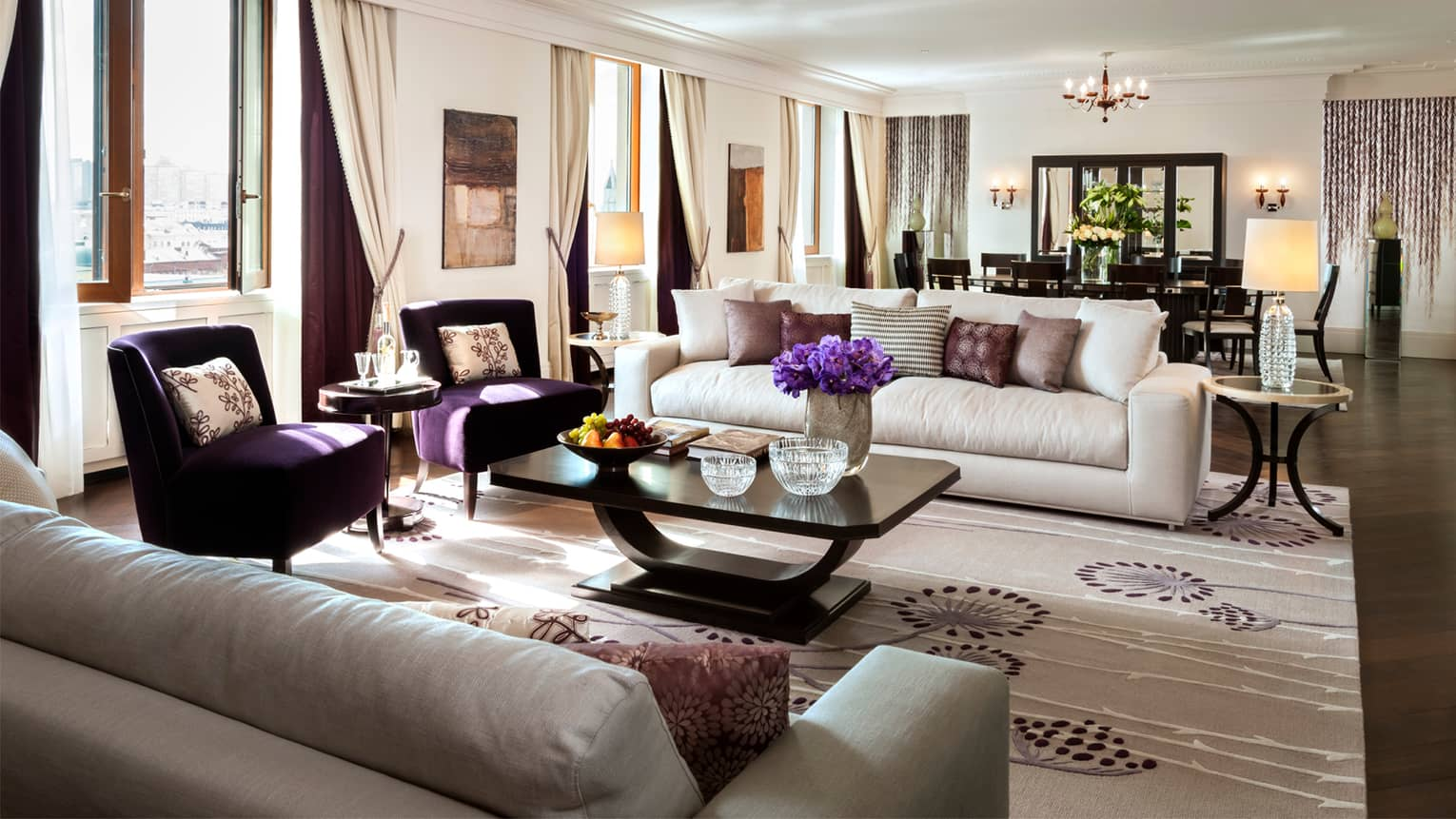 Imperial Suite living area with white sofas, dark purple armchairs, private dining table for 10