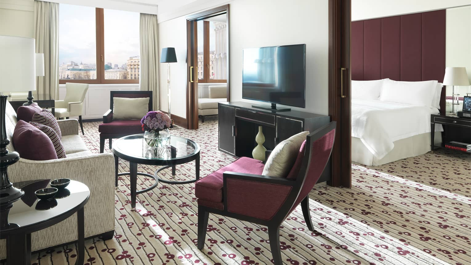 Executive Suite living area with burgundy accent chairs, flowers in glass vase, flat-screen TV on wall concealing bed