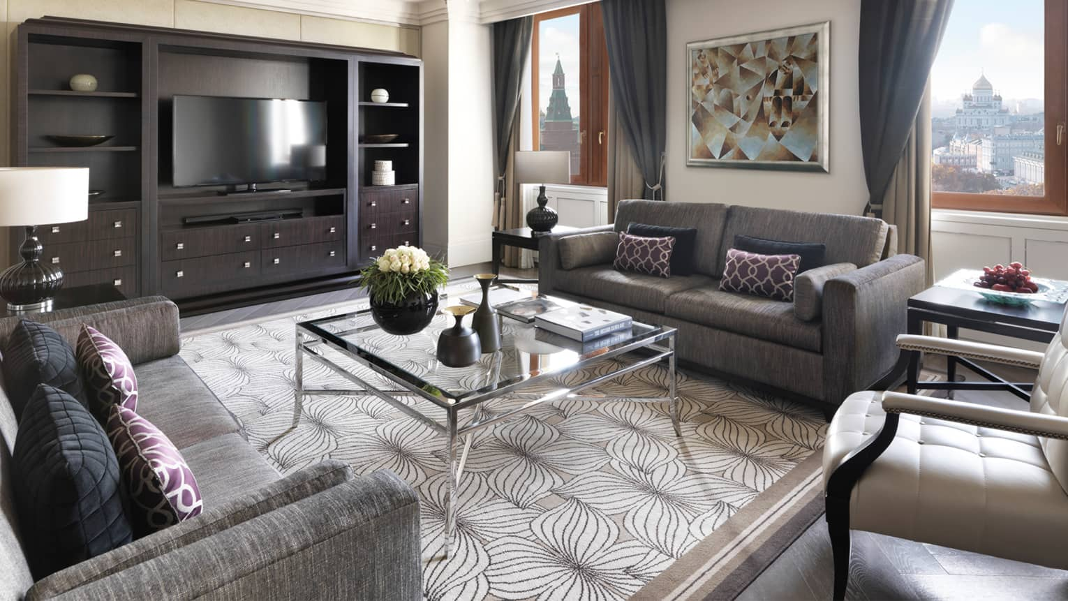 Hotel suite living room with grey sofas, glass coffee table, wall unit with flat-screen TV