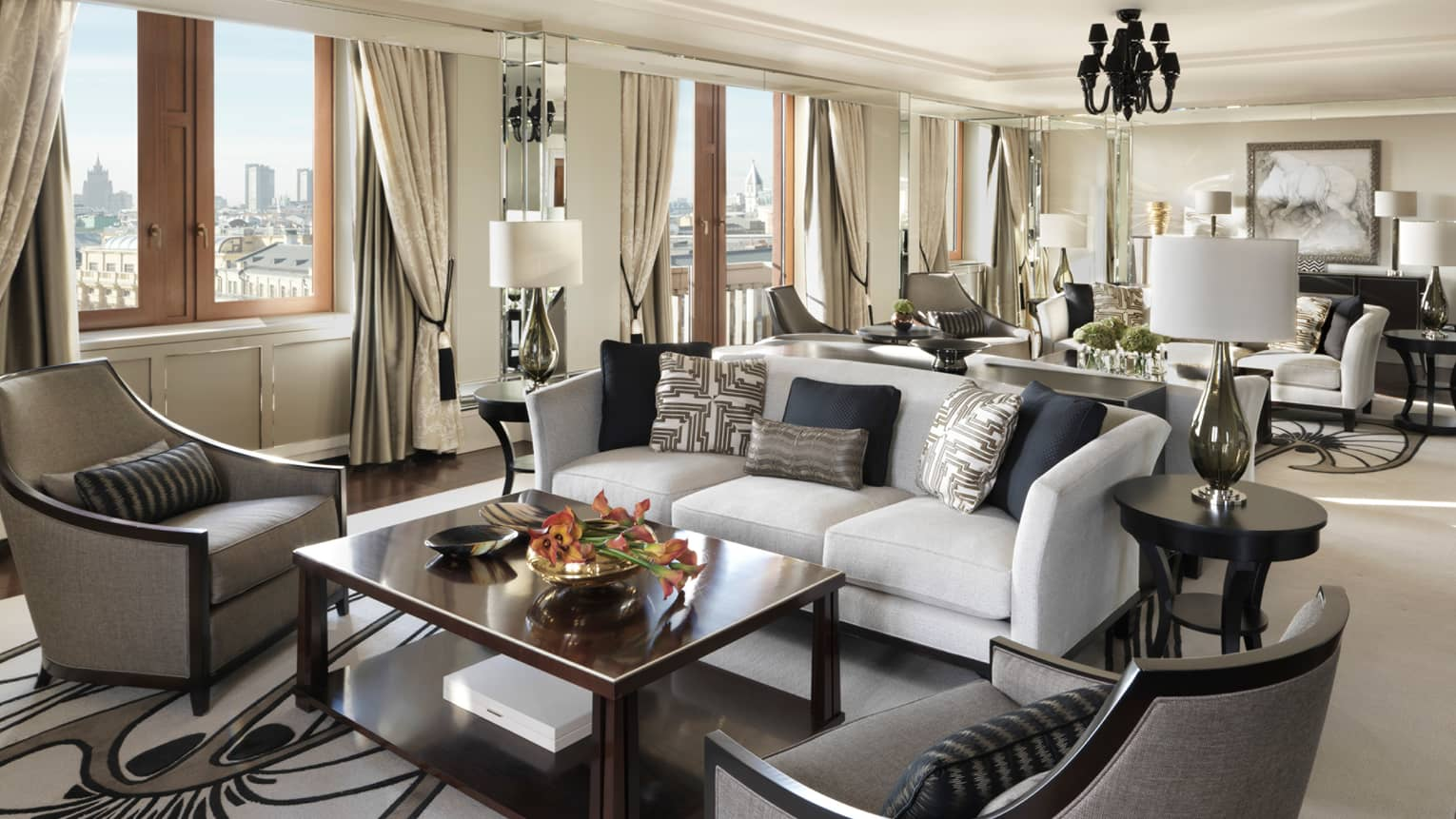 Pozharsky Royal Suite living area with white sofa, grey armchairs, private dining area in background