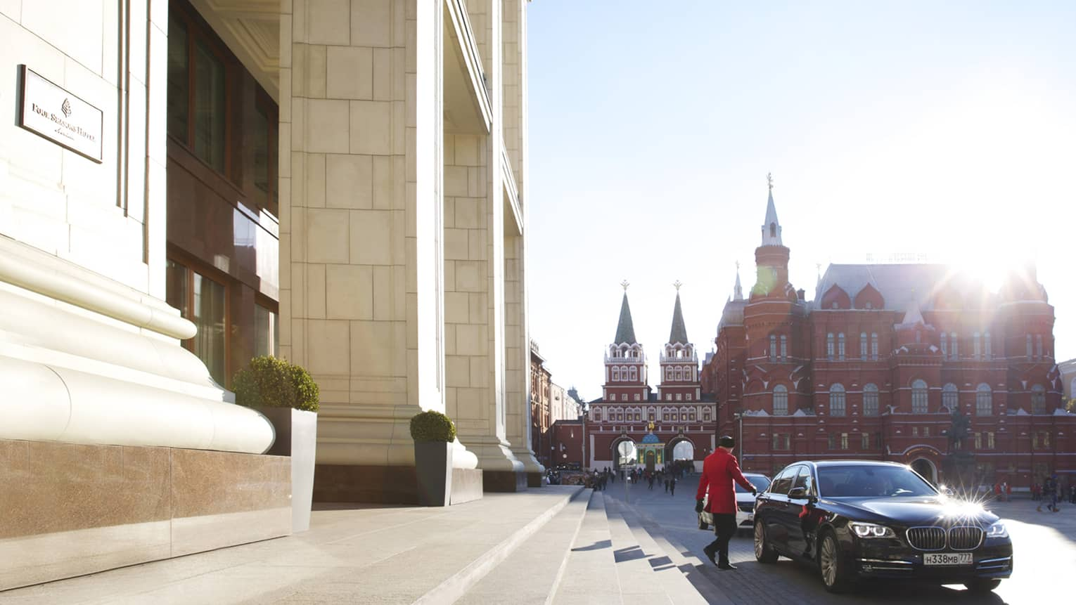 Sunny Four Seasons Hotel Moscow, doorman wearing red jacket walks towards luxury car