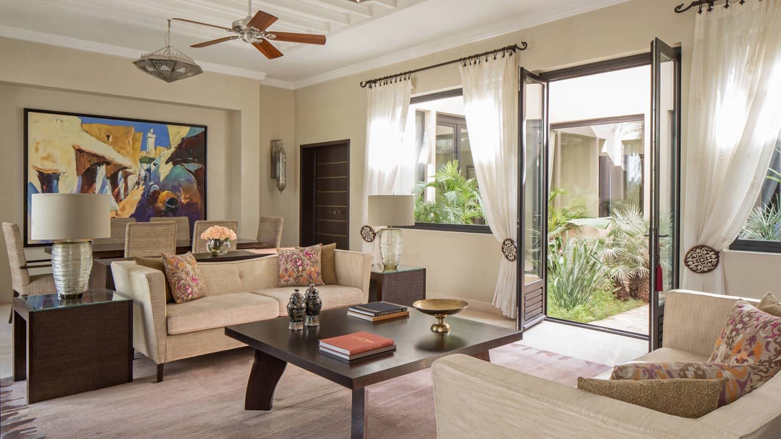 Two Bedroom Villa living room with two sofas around large coffee table with books, dining table, large colourful painting