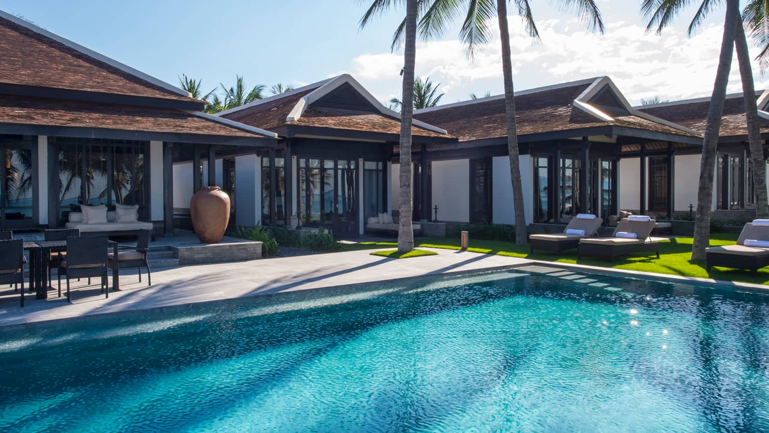 Five bedroom pool villa exterior. tall palm trees around outdoor swimming pool
