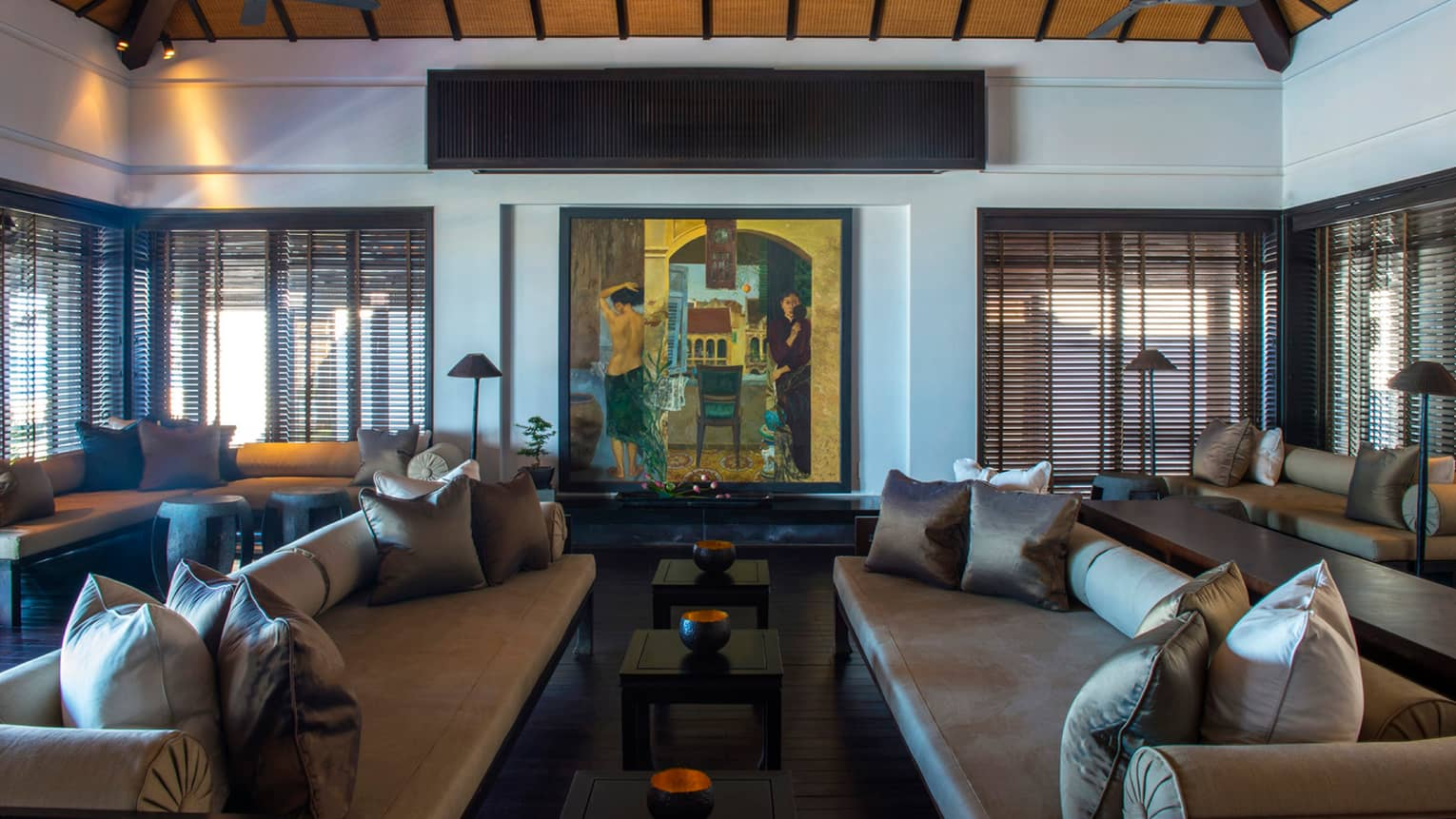 Large colourful oil painting on wall over two sofas, tables with brass bowls, under soaring wood ceilings