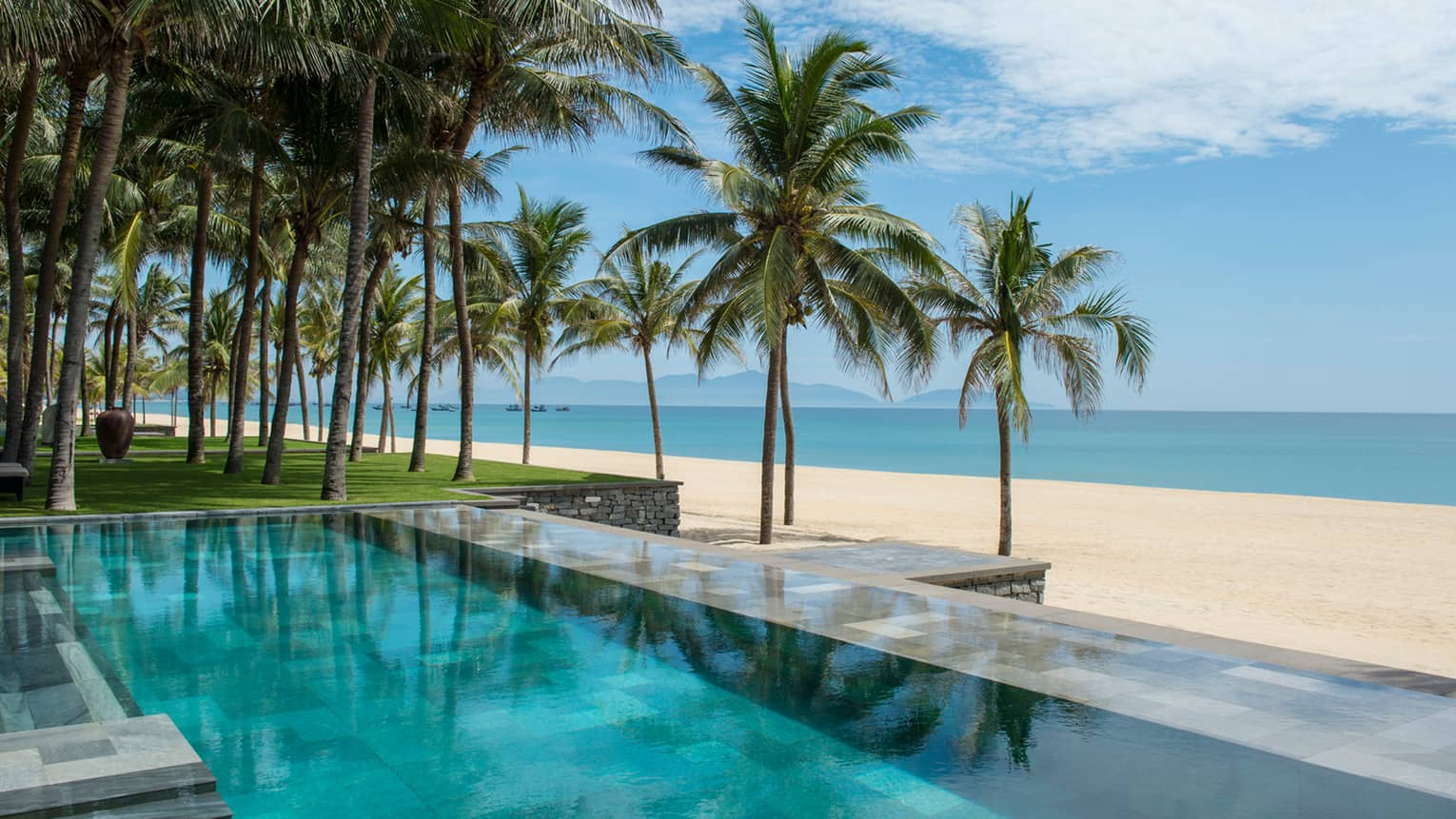 Tall palm trees between stone outdoor swimming pool and white sand beach