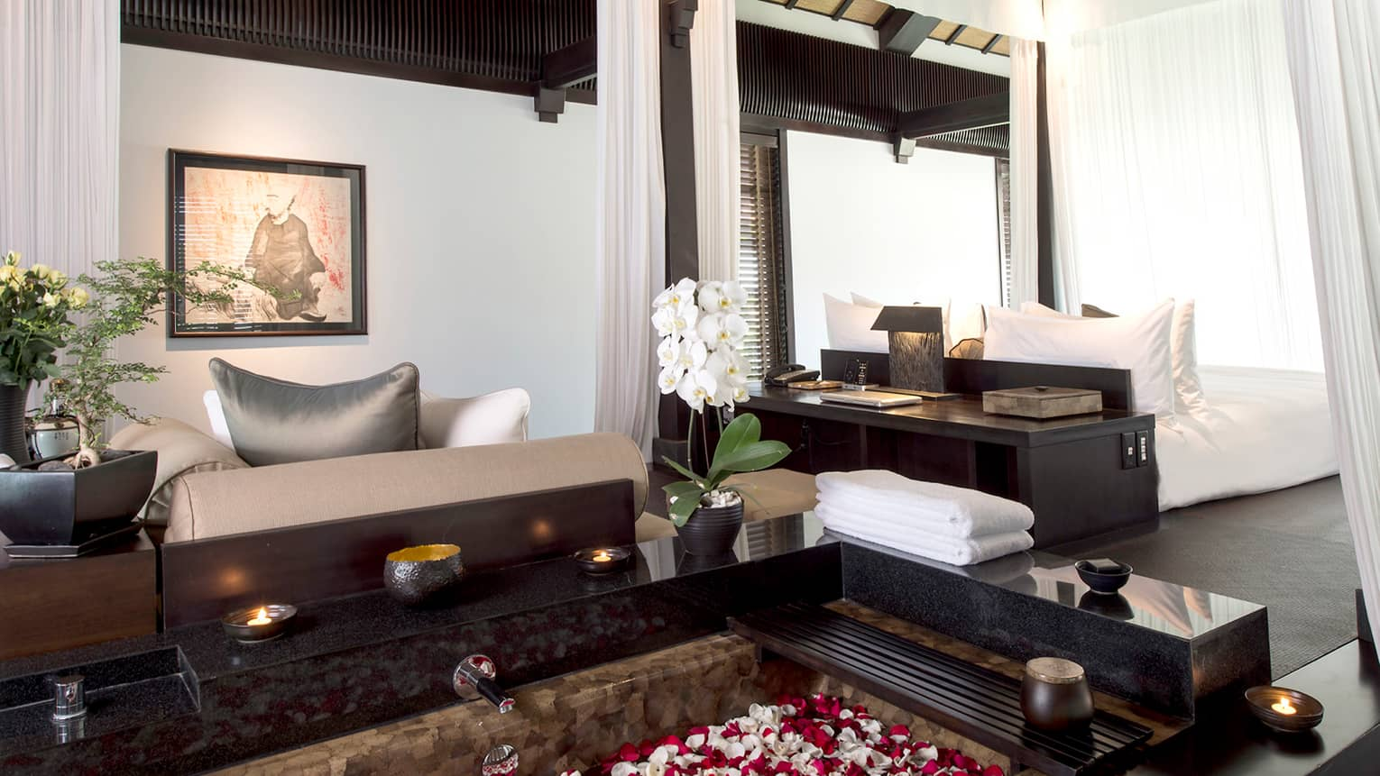 Pool Villa candle-lit tub filled with flower petals in middle of bright room, sofas