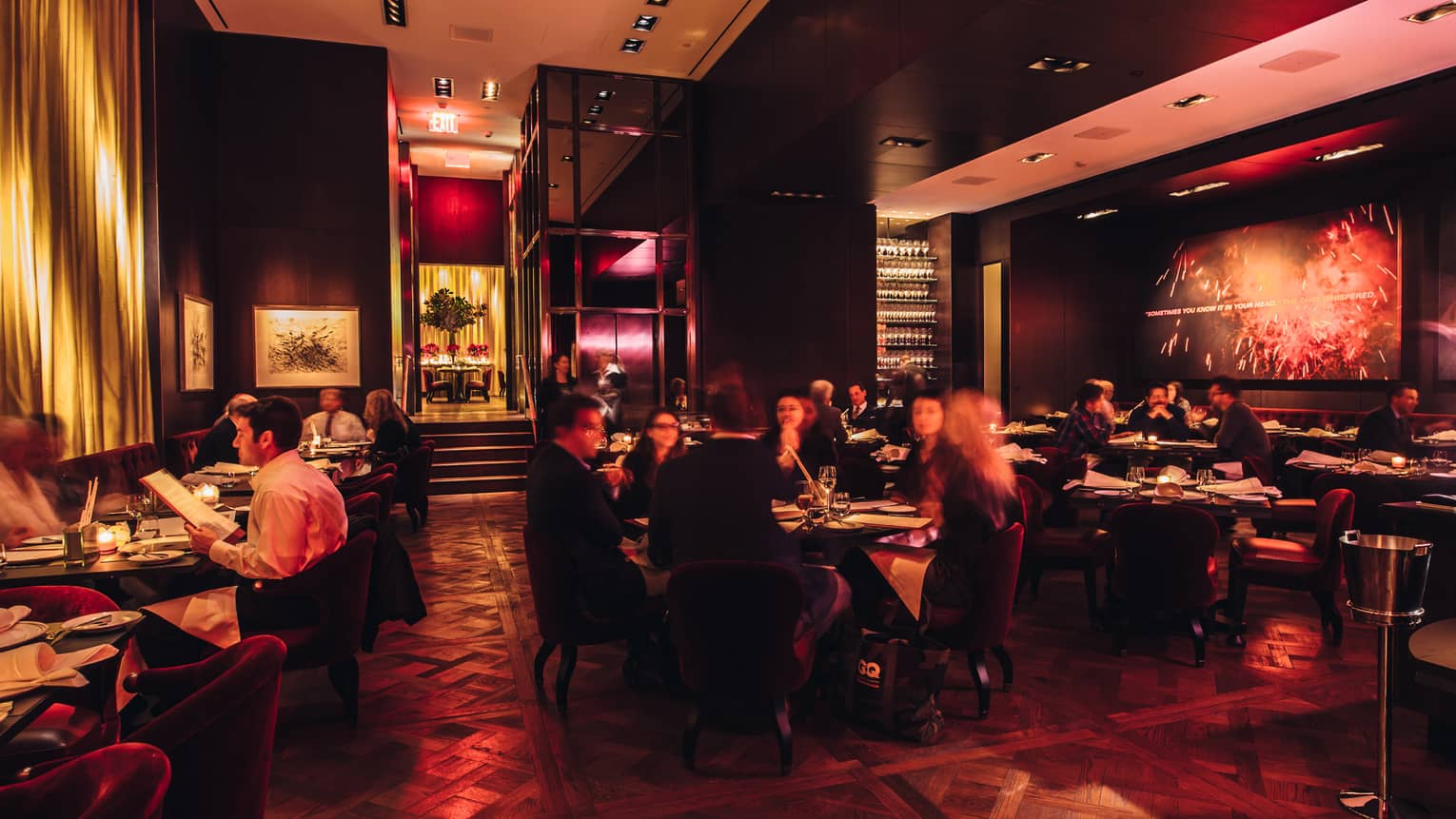 Diners at tables in dark CUT by Wolfgang Puck restaurant with purple, red lighting