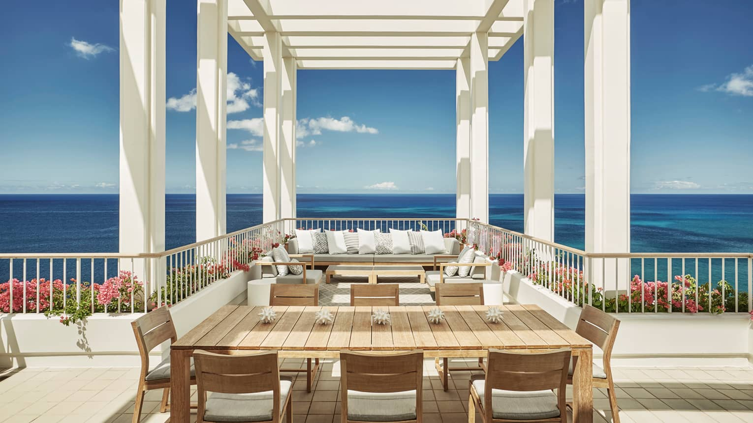 Penthouse Suite large patio dining table, seating area under white pergola, blue sky