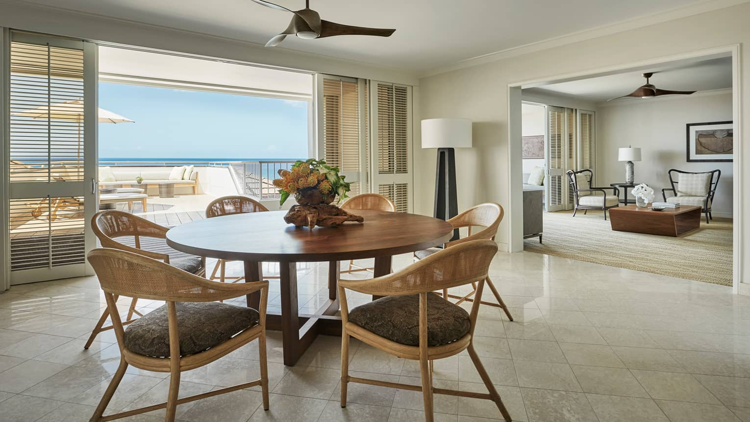 Residence dining room with round wood table retro wicker seats, sliding balcony shutters