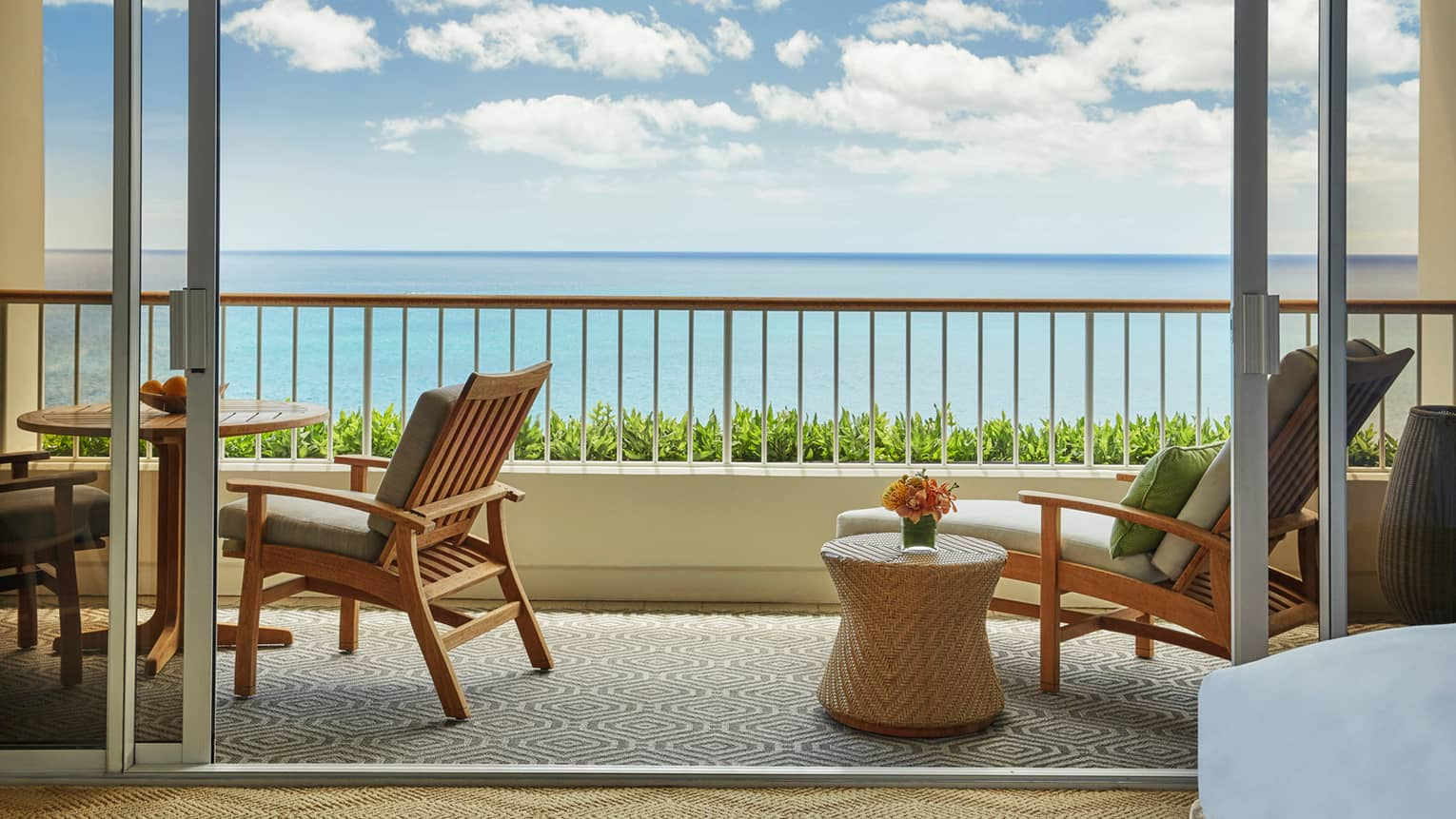 Junior Suite balcony with wood and wicker lounge furniture, ocean views