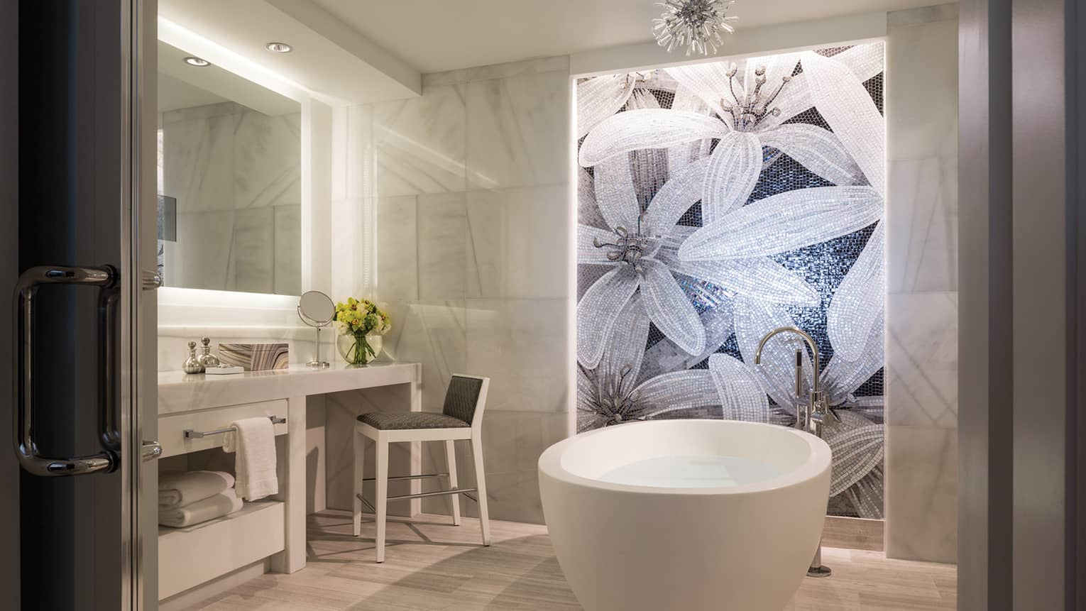 Grand Suite master bathroom white free-standing tub under mosaic tile wall with floral pattern, vanity