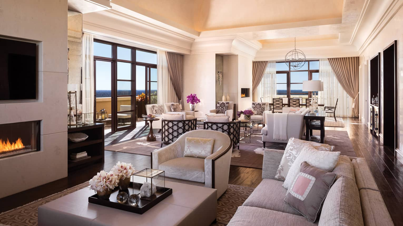 Presidential Suite sofa, armchair, large ottoman table by gas fireplace, TV in front of dining room