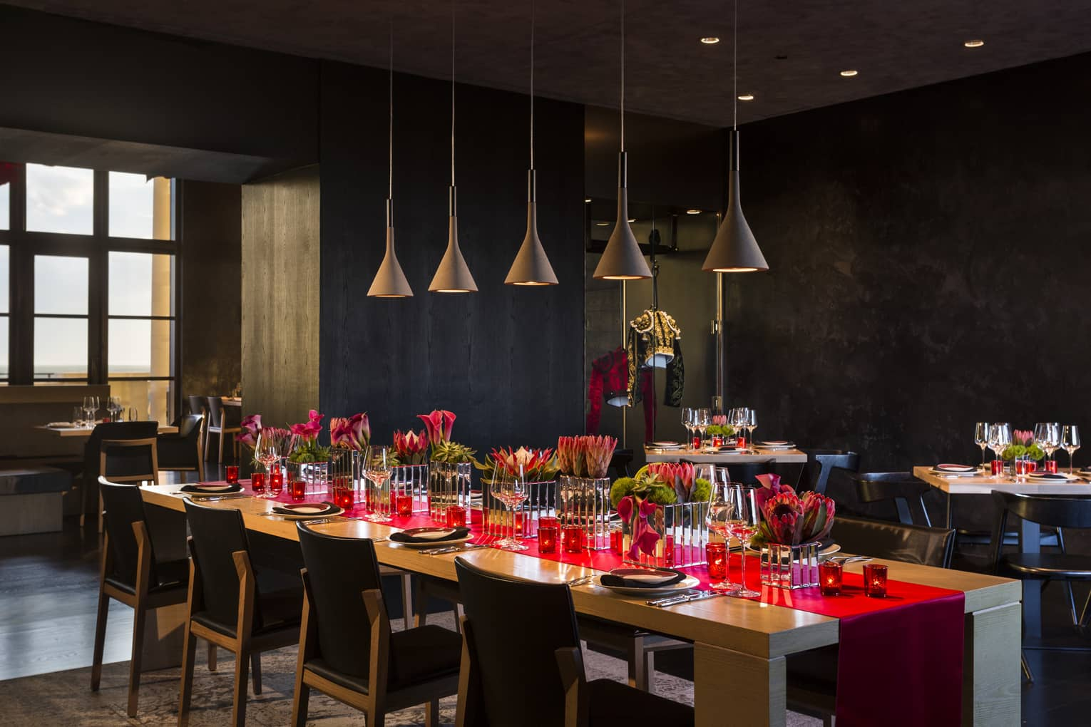 Long table with red runner under row of lamps in San Sebastian private dining room