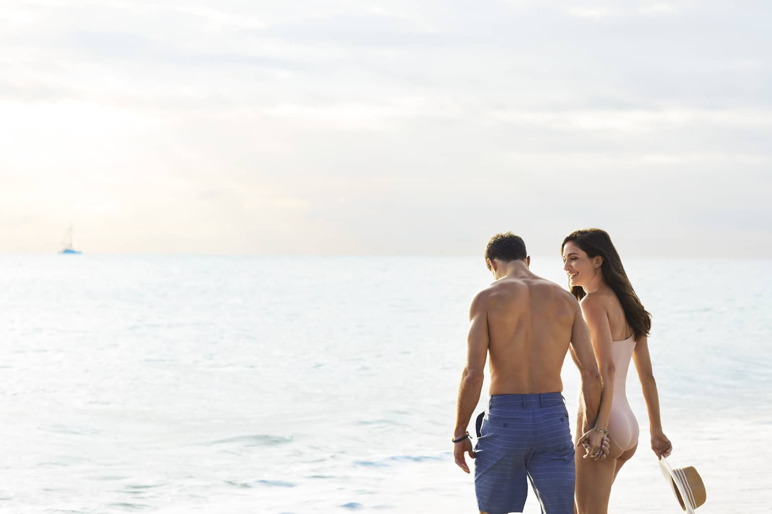 A couple holds hands as they walk along the beach