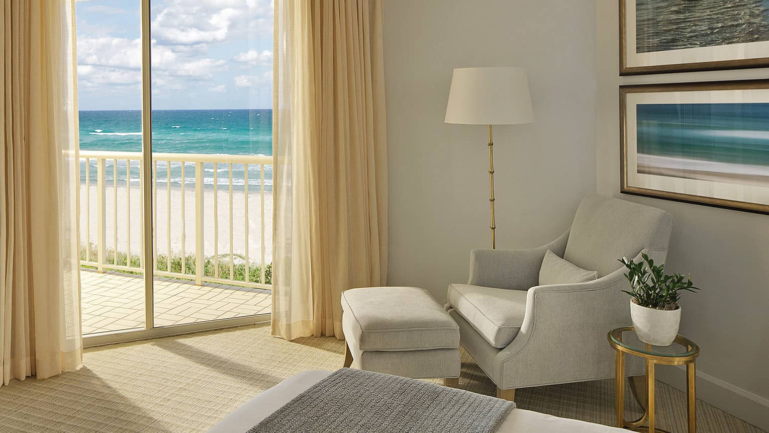 White armchair next to glass balcony door with view of ocean and beach