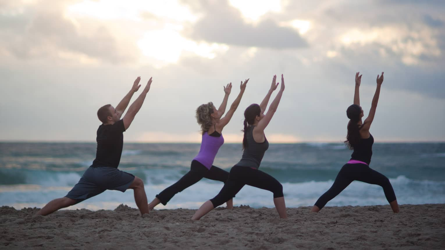 Man in three women in workout clothes do yoga stretch on beach in morning
