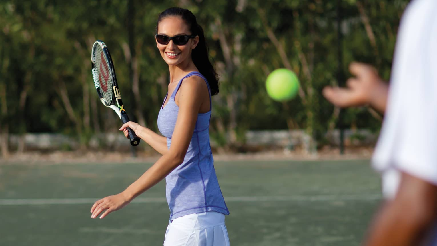 Woman in sunglasses and swings tennis racket as tennis ball approaches