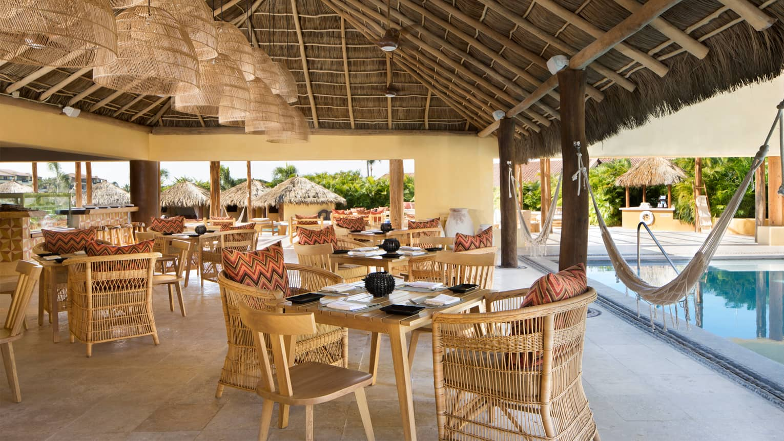 Tamai Pool Bar light wicker dining chairs and tables under thatched roof cabana by pool, hammocks