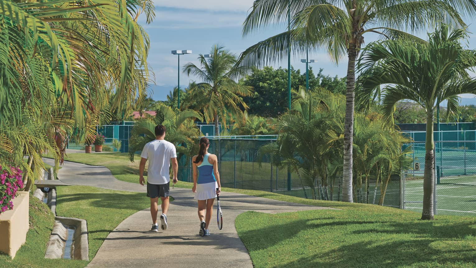 Man and woman holding tennis racket walk down path toward tennis courts, past palm trees